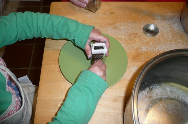 Here is a child using a small spice grater to grate the nutmeg.